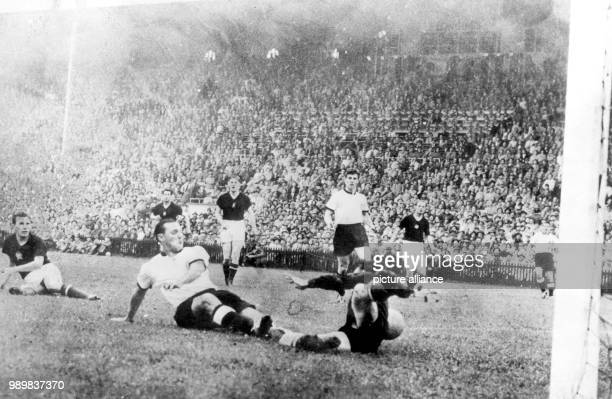 German midfielder Max Morlock falls to the ground and pushes the ball into the net past diving Hungarian goalkeeper Gyula Grosics and scores the 12...