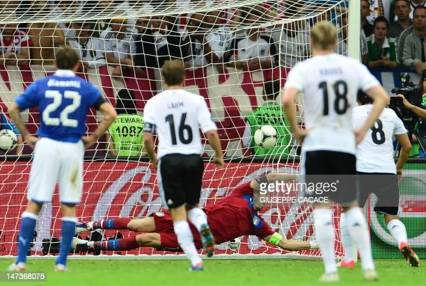 German midfielder Mesut Oezil scores a penalty shot during the Euro 2012 football championships semi-final match Germany vs Italy on June 28, 2012 at...