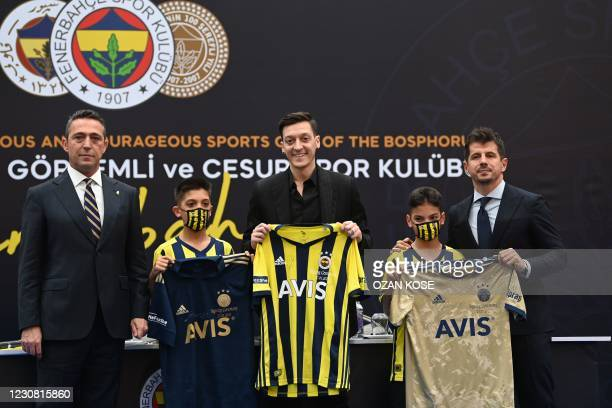 German midfielder Mesut Ozil holds his new jersey as he poses with Fenerbahce's president Ali Koc and sport director Emre Belezoglu , during a press...