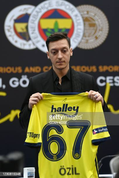 German midfielder Mesut Ozil poses with his jersey after signing his new three-and-a-half year contract with Turkish football club Fenerbahce at the...