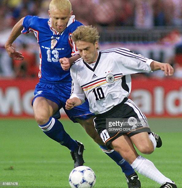German midfielder Thomas Hassler is challenged by Croatian opponent Mario Stanic during the 1998 Soccer World Cup quarterfinal match between Germany...
