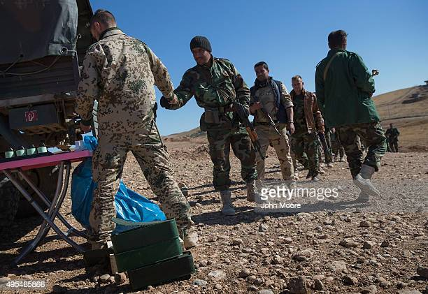 German military instructor hands out ammunition to Kurdish Peshmerga forces during the last week of a military training course on November 3 2015 in...