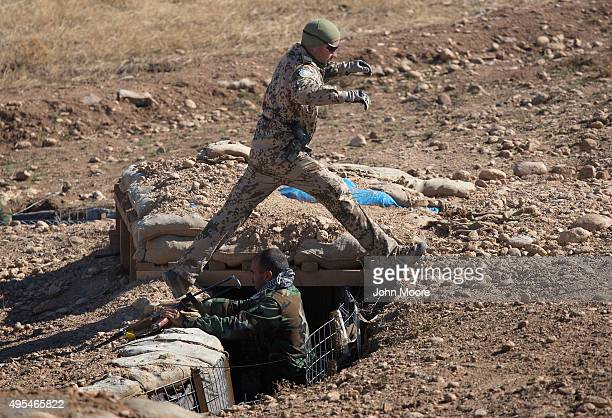 German military instructor steps over a trench as Kurdish Peshmerga forces take positions during the last week of a military training course on...