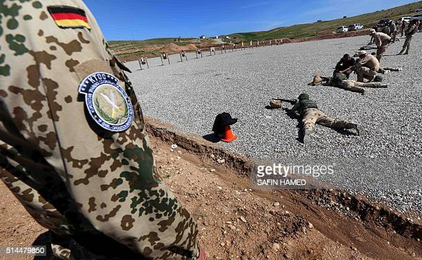 German military trainer looks at Kurdish Peshmerga fighters shooting during a training session on machine guns at a camp on the outskirts of Arbil,...