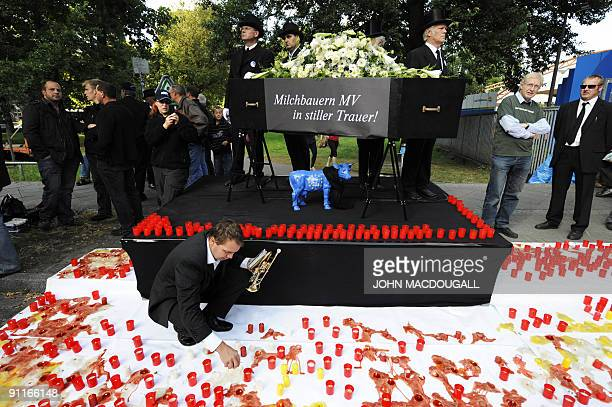German milk farmers stage a protest with a mock coffin outside the venue where German Chancellor Angela Merkel and her Christian democrats Union...