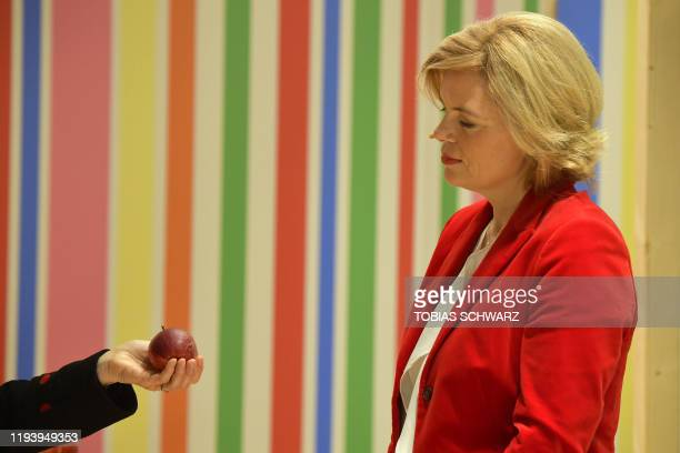 TOPSHOT German Minister for Food and Agriculture Julia Kloeckner is offered an apple as she visits the Gruene Woche international agriculture fair in...
