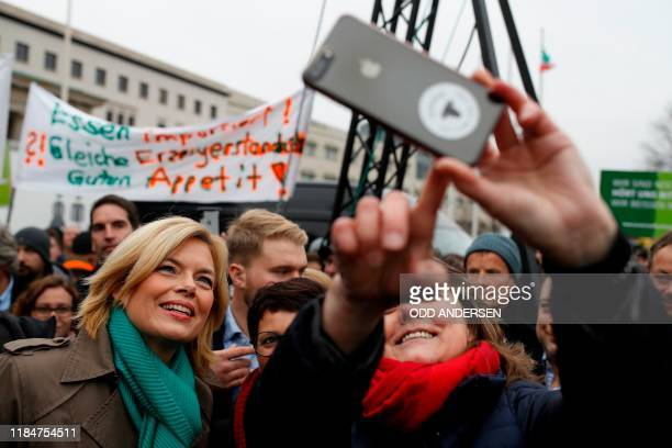 German Minister for Food and Agriculture Julia Kloeckner takes a selfie with some protesters near the Brandenburg Gate in occasion of the...
