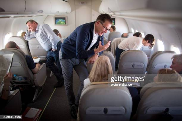 German Minister of Health Hermann Groehe and Minister of Development Gerd Mueller speak with the media and members of the delegation during a flight...