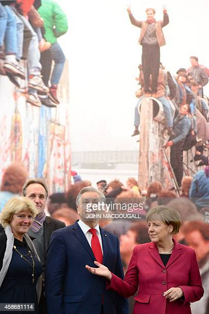 German Minister of State for Culture Monika Gruetter Berlin Mayor Klaus Wowereit and German Chancellor Angela Merkel stand by a giant reproduction of...