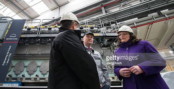 German Minister of Work and Social Issues Andrea Nahles speaks to CEO of MAN Diesel Turbo SE Uwe Lauber and workers while visiting the production at...