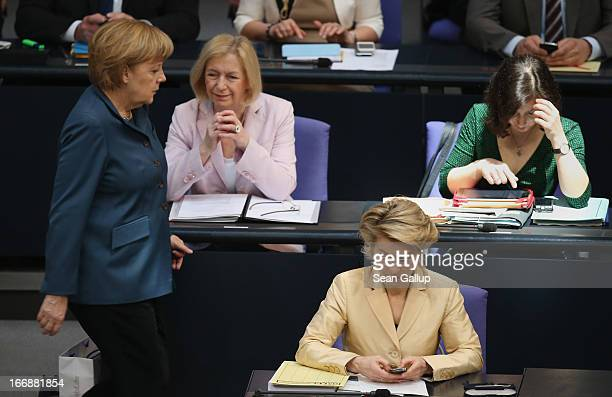 German Minister of Work and Social Issues Ursula von der Leyen operates a smartphone as German Chancellor Angela Merkel walks by and other female...