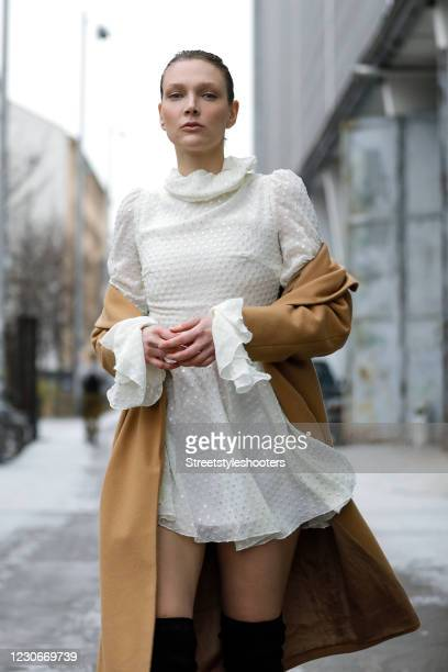 German model and actress Victoria Jancke wearing a camel colored long coat by Vero Moda and a short cream colored dress with ruffle details at the...