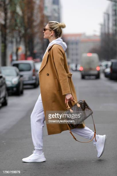 German model and actress Victoria Jancke wearing a white hoodie by Asos, white pants by Asos, white socks by Wrangler, a camel colored long coat by...