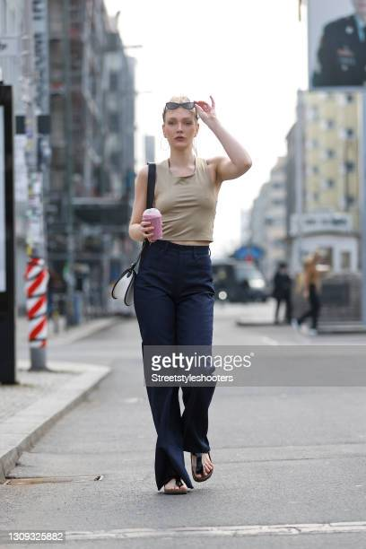 German model and actress Victoria Jancke wearing dark blue denim jeans flared pants by G-Star RAW, a beige crop top by Selected, a black and white...