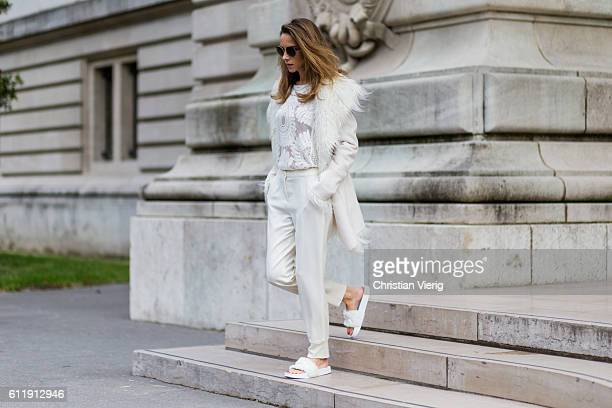 German model and fashion blogger Alexandra Lapp wearing a white fur jacket from Marc Aurel Chloe sunglasses laced sheer top white pants and Puma...