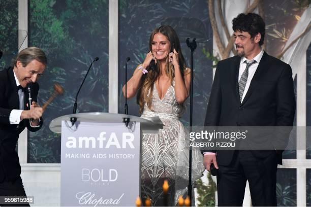 German model Heidi Klum and USPuerto Rican actor Benicio Del Toro conduct an auction on May 17 2018 during the amfAR 25th Annual Cinema Against AIDS...