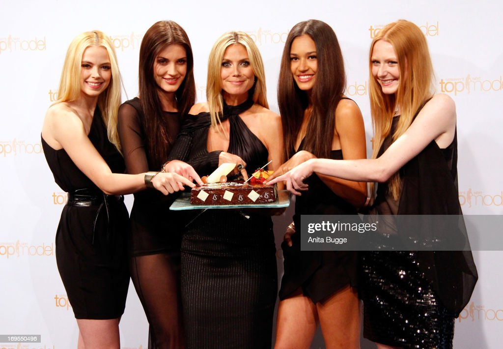German model Heidi Klum (C) poses with (L to R) contestants Sabrina Elsner, Luise Will, Lovelyn Enebechi and Maike van Grieken with a birthday cake prior to Klum's June 1 birthday at a photo call for the reality television show and modeling competition 'Germany's Next Topmodel' at Waldorf Astoria on May 27, 2013 in Berlin, Germany.