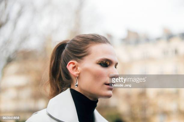 German model Lena Hardt wears the gold flake eye makeup from the Akris show Lemaire Silver Short Drop Earrings and a white Celine leather jacket on...