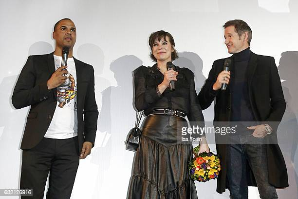 German moderator Patrice Bouedibela US actress Milla Jovovich and her husband producer Paul W S Anderson during the stage presentation at the Social...