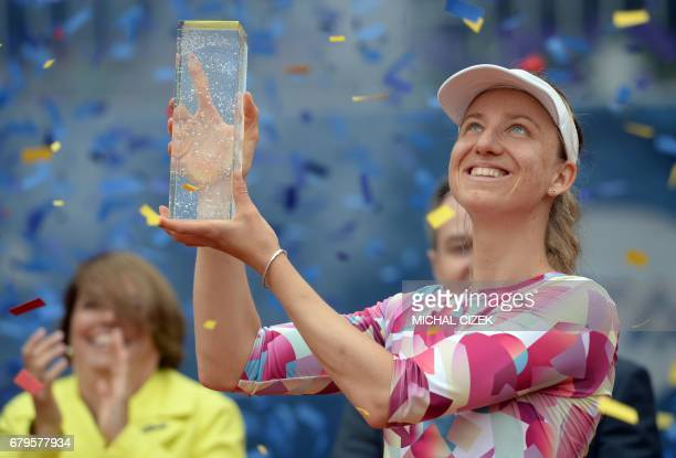 German Mona Barthel poses with the trophy after winning over Czech's Kristyna Pliskova during their final tennis match at the Prague Open on May 6...