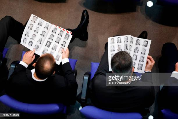 German MPs look at a book of MPs' portraits during the first session of the newlyelected parliament on October 24 2017 at the Bundestag in Berlin...