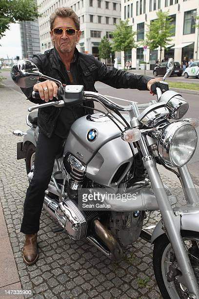 German musician Peter Maffay poses on a photographer's motorcycle upon his arrival to speak to the media about his charity project symposium for...