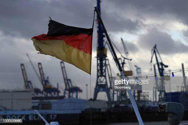A German national flag flies from a boat near shipping cranes at the port of Hamburg in Hamburg Germany on Wednesday Feb 12 2020 Germany's biggest...