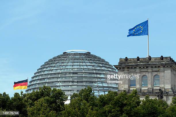 A German national flag left and a European Union flag fly alongside the dome of the Reichstag Germany's parliament building in Berlin Germany on...