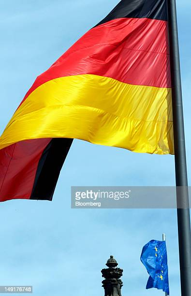 A German national flag right and a European Union flag fly above the Reichstag Germany's parliament building in Berlin Germany on Tuesday July 24...
