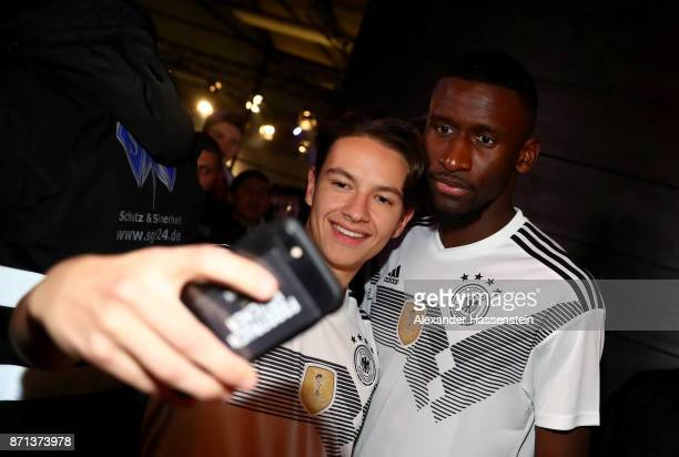 German National Football Team Player Antonio Ruediger poses with a fan at the presentation of the 2018 FIFA World Cup Russia Adidas jersey at The...