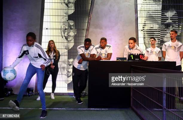 German national football team players look on as a fan plays with a ball at the presentation of the 2018 FIFA World Cup Russia Adidas jersey at The...
