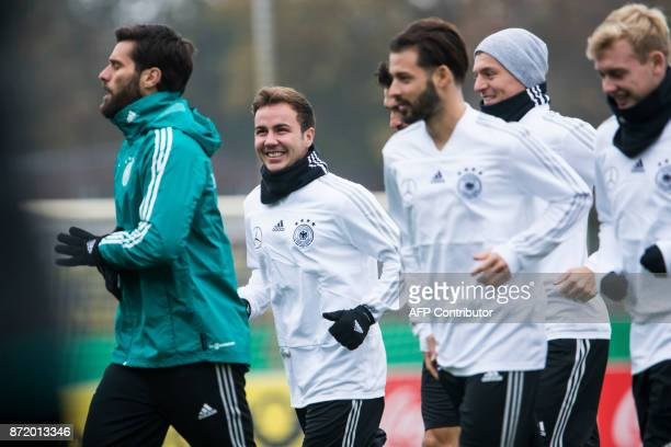 German national football team's midfielder Mario Goetze and teammates warm up during a training session on November 9 2017 at the training grounds of...