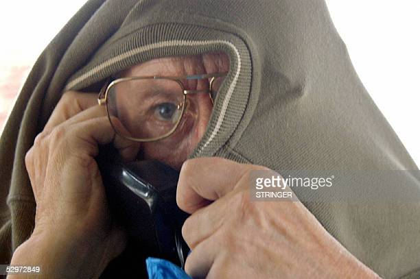 German national Leo Brock attempts to hide his face 24 May 2005 as he appears before the Kilifi resident Magistrate in Mombasa to face a count of...