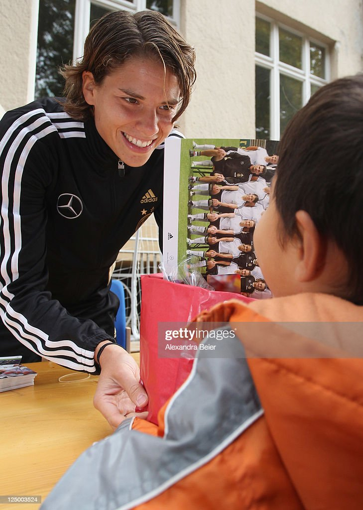 German national soccer player Annike Krahn hands over a bag filled with healthy food to a first grade pupil on September 15, 2011 in Augsburg, Germany.