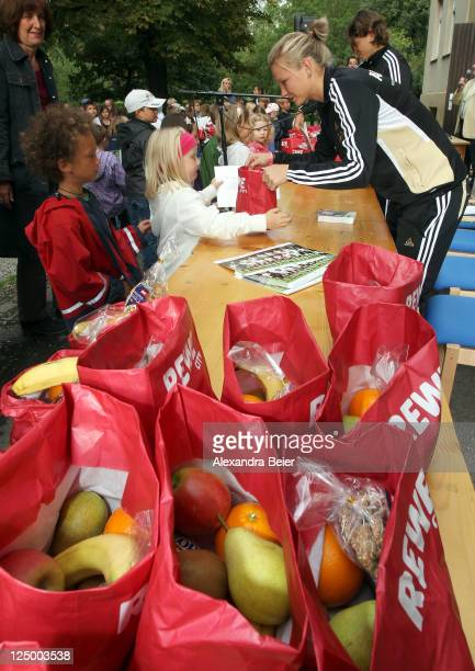 German national soccer players Annike Krahn and Alexandra Popp hand over bags filled with healthy food to first grade pupils on September 15 2011 in...
