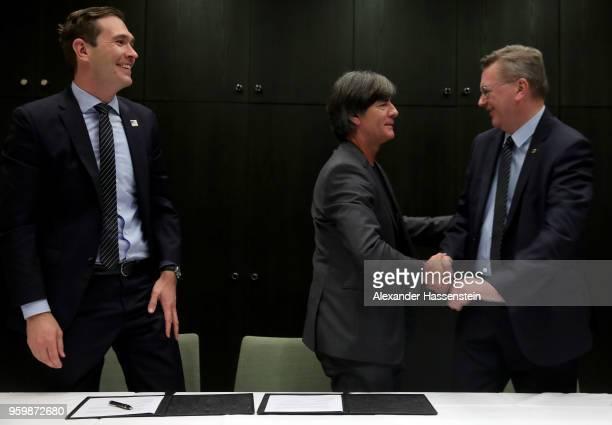 German national team head coach Joachim Loew and DFB president Reinhard Grindel shake hands whilst DFB general secretary Dr. Friedrich Curtius looks...