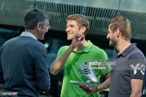 German national team soccer player Thomas Mueller stands during an award ceremony to honor his world cup performance next to his brother Simon...
