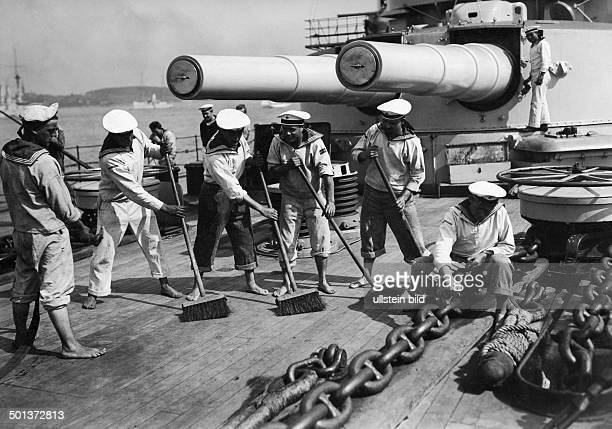 the deck of the battleship SMS Braunschweig is swabbed by sailors There are an anchor chain and a turret with two guns on the deck undated probably...