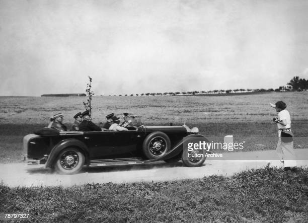 German Nazi leader Adolf Hitler is saluted by a supporter at the roadside while driving to visit the ailing German President Paul von Hindenburg at...