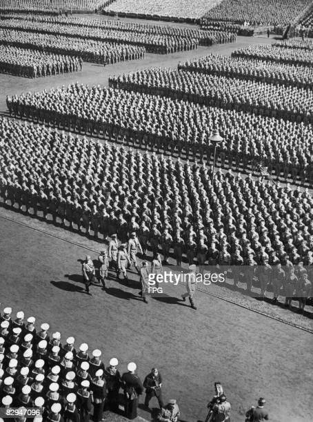German Nazi leader Adolf Hitler reviews Hitler Youth formations at a Nuremberg Rally circa 1935 Immediately behind Hitler are Rudolf Hess and Hitler...