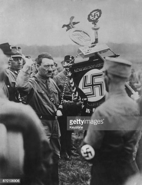 German Nazi Party leader Adolf Hitler hands over the Sturmabteilung emblem to to one of his leaders during a mass rally at Braunschweig or Brunswick...