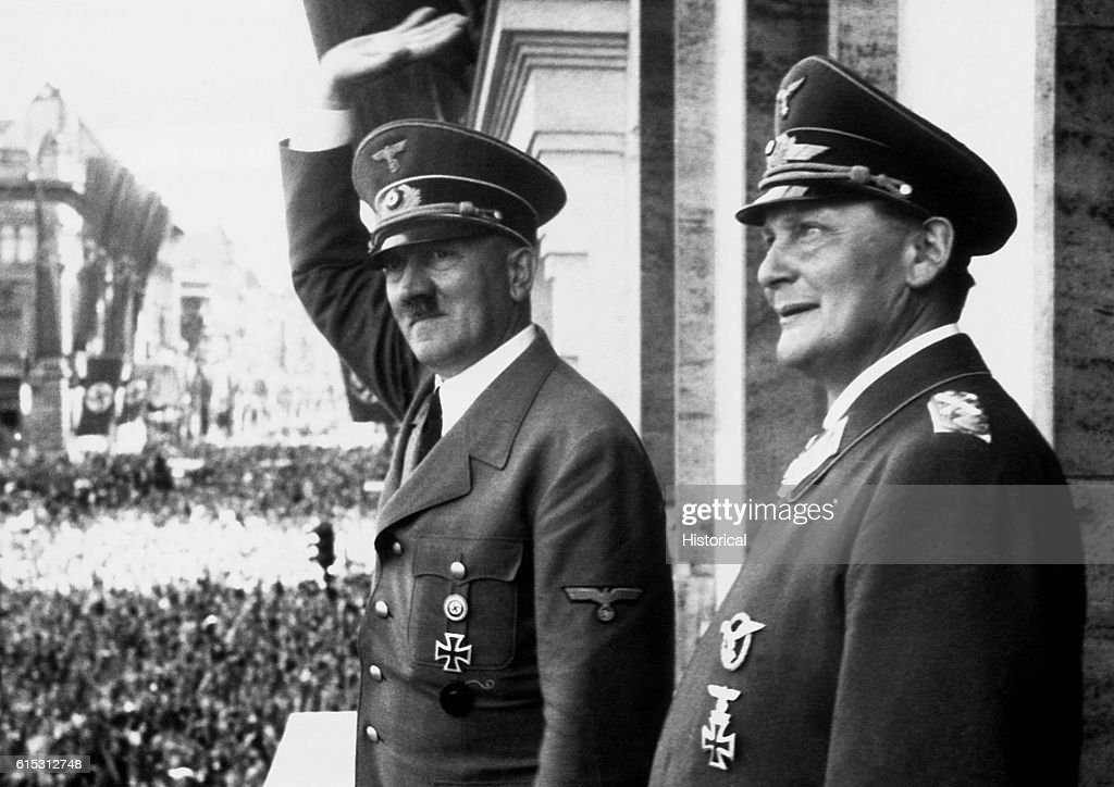 German Nazi party leader Adolf Hitler waves to a crowd from a balcony as Storm Trooper commander and Reichstag president Hermann Goering stands by.