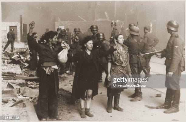 German Nazi SS troops guarding members of the Jewish resistance captured during the suppression of the Warsaw ghetto uprising in 1943. About 13,000...