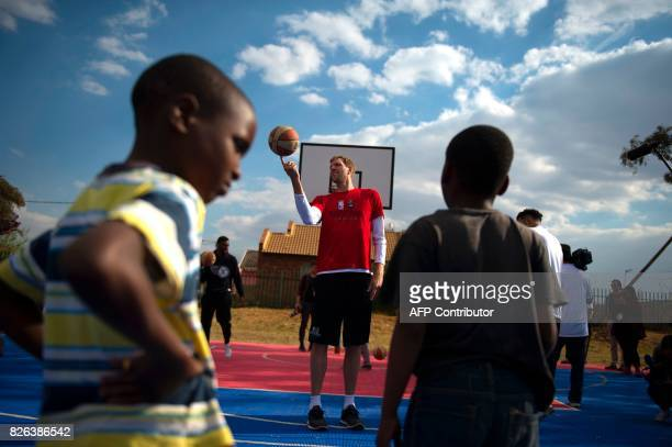 German NBA player Dirk Nowitzki of the Dallas Mavericks and other NBA players from various countries interact with children during a basketball...