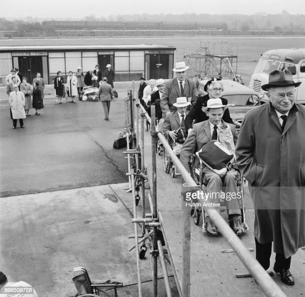 German neurologist Ludwig Guttmann leads members of the Britain's team, en route to Perth for the '1962 Commonwealth Paraplegic Games', on the...