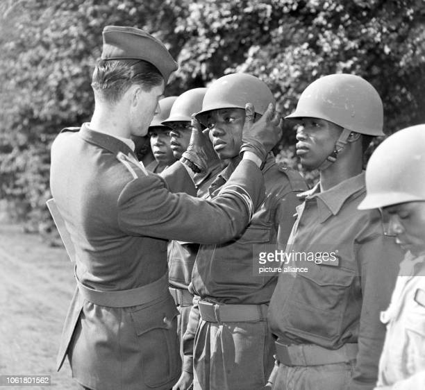 A German noncommissioned officer adjusts the helmets of Nigerian soldiers on 3 September 1963 Ninety Nigerian soldiers are trained as pilots or...