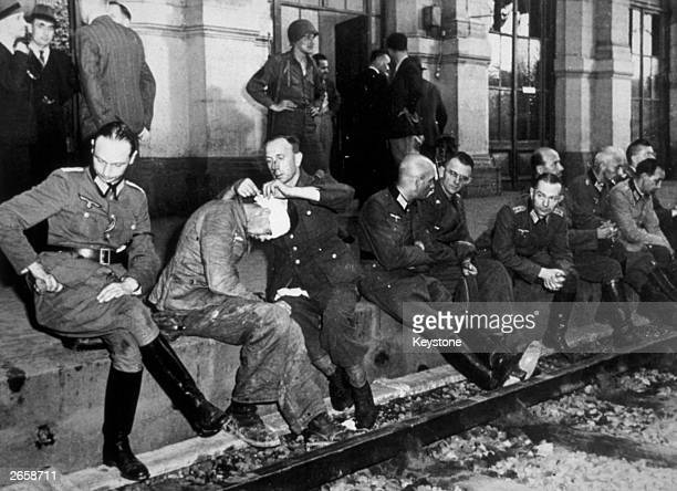 A German officer bandages the wounds of another as the staff of General von Choltitz sit on the platform at the Montparnasse station following the...