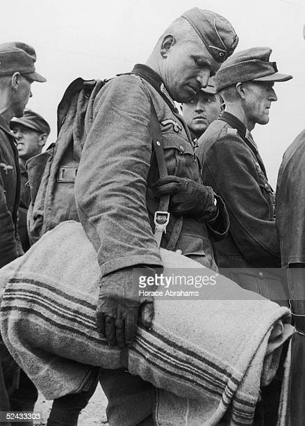 A German officer carrying a blanket waits with other prisoners of war on arrival at a British port from France July 1944