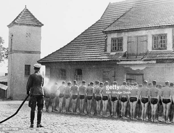 German officer hoses down new recruits at training camp during World War II, ca. 1939