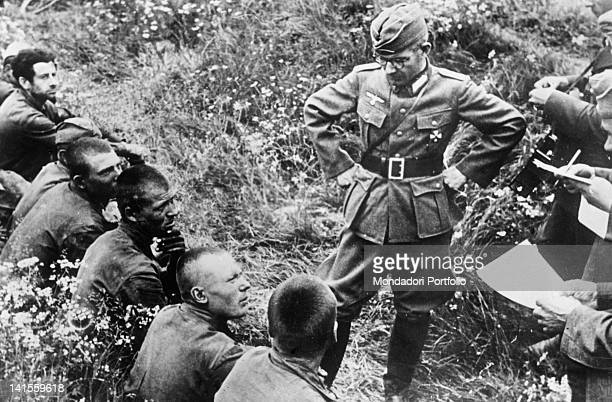 A German officer interrogating a group of Soviet prisoners captured in the Moscow area Russia august 1942